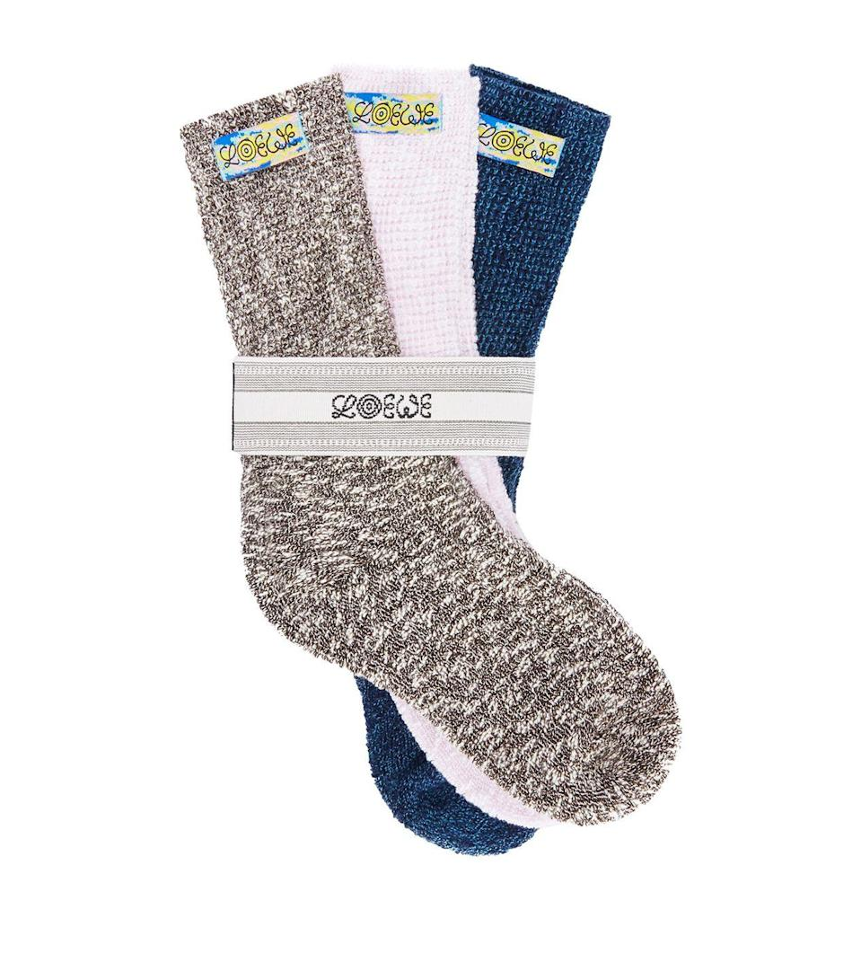 """<p>Lazy evenings beside the fireplace armed with a book, a glass of your favourite tipple and your feet wrapped up in a pair of cosy socks is heaven personified. Loewe delivers a premium addition to your sock drawer with these exquisitely woven thick cotton-blend ribbed socks that offer superior warmth and comfort all day long. </p><p>£125, <a href=""""https://www.harrods.com/en-gb/shopping/loewe-knitted-socks-pack-of-3-16094602"""" rel=""""nofollow noopener"""" target=""""_blank"""" data-ylk=""""slk:Loewe"""" class=""""link rapid-noclick-resp"""">Loewe</a>.</p>"""