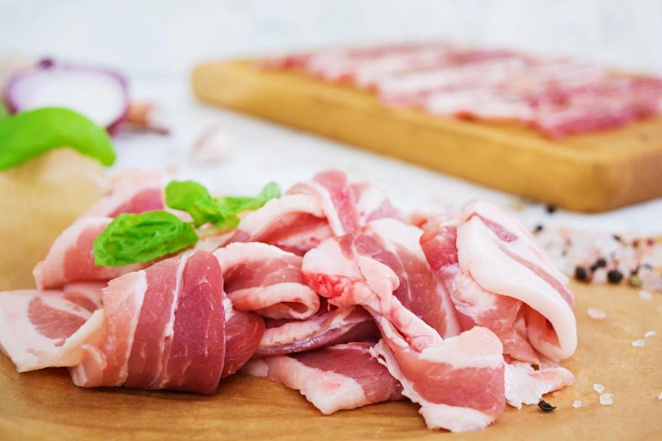Fresh sliced bacon with spices on white background