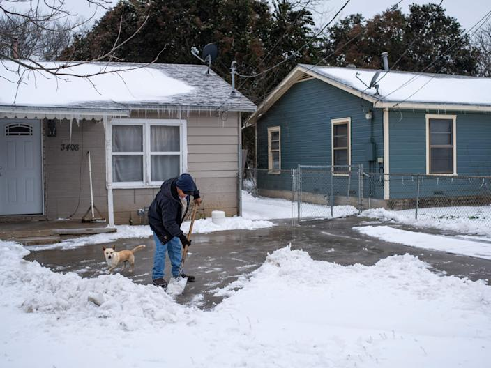 <p>A Waco, Texas, resident clears snow from his driveway alongside his dog on February 17, 2021 as severe winter weather conditions over the last few days has forced road closures and power outages over the state.</p> (AFP Via Getty)