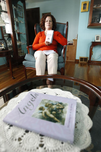"Lillie Leonardi sits behind a table that has a book on angels in her living room as she shows some copies of her book ""In the Shadow of a Badge: A Spiritual Memoir,"" on Tuesday, July 3, 2012, in Arnold, Pa. Leonardi, a former police officer who retired from the FBI due to post-traumatic stress disorder from her time as a liaison between law enforcement and the victims of United Airlines Flight 93 has written a book about seeing legions of angels guarding the site where the hijacked airliner crashed on Sept. 11, 2001. (AP Photo/Keith Srakocic)"