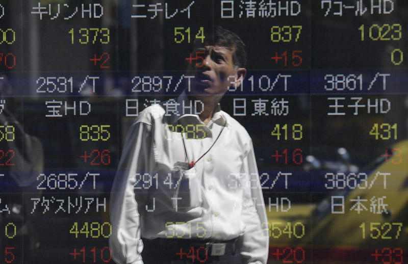 A passer-by is reflected on the electronic stock board of a securities firm in Tokyo, Wednesday, Sept. 18, 2013. Asian stock markets struggled to find their footing Wednesday as traders hesitated to make bold moves before the Federal Reserve winds up a crucial policy meeting later in the day. (AP Photo/Shizuo Kambayashi)
