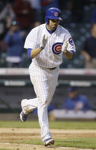 Chicago Cubs' David DeJesus celebrates as he walks to first base during the 11th inning of a baseball game against the Los Angeles Dodgers in Chicago, Sunday, May 6, 2012. The Cubs won 4-3. (AP Photo/Nam Y. Huh)