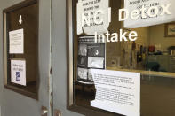In this May 7, 2020, photo signs hang on doors at the Na'Nizhoozhi Center detox facility in Gallup, N.M. A night of revelry before bars and restaurants shut in New Mexico appears to have led to an outbreak in the detox center and homeless shelter on the fringes of the Navajo Nation. (AP Photo/Morgan Lee)