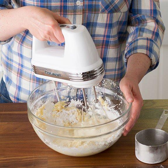 Person just beating the sugar into the mixture with a hand mixer with a metal measuring cup nearby