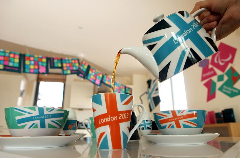 A woman pours tea from a London 2012 branded tea set at the launch of the London Olympic Games official merchandise on July 30, 2010 in London, England. (Photo by Oli Scarff/Getty Images)