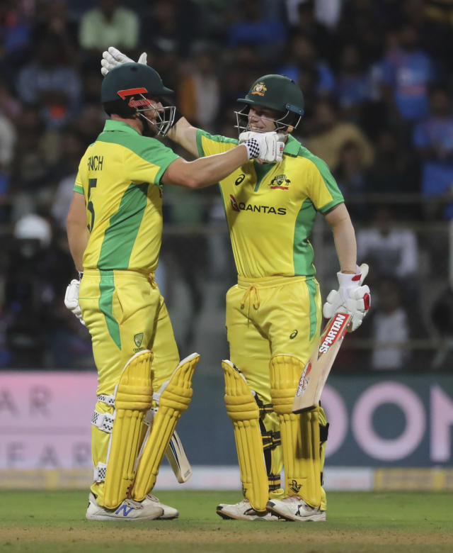 Australia's captain Aaron Finch, left, is greeted by David Warner after scoring hundred runs during the first one-day international cricket match between India and Australia in Mumbai, India, Tuesday, Jan. 14, 2020. (AP Photo/Rafiq Maqbool)