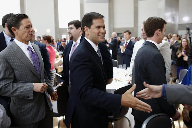 "Sen. Marco Rubio, R-Fla., center, greets attendees as he is followed by Ralph Reed, founder of the Faith and Freedom Coalition, left, after he spoke at the ""Road to Majority"" conference in Washington, Thursday, June 13, 2013. The fight for the direction of the Republican Party will be on display Thursday at a Washington conference hosted by the Faith and Freedom Coalition, a group created by former Christian Coalition leader Ralph Reed. Designed to strengthen the evangelical influence in national politics, the conference gives many religious conservative activists their first look at potential 2016 presidential candidates. (AP Photo/Charles Dharapak)"