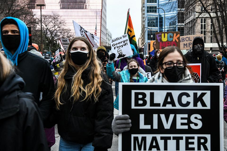 People hold placards as they protest outside of the Courthouse during the trial of former Minneapolis police officer charged with murdering George Floyd in Minneapolis, Minnesota on April 19, 2021.(Chandan Khanna/AFP via Getty Images)