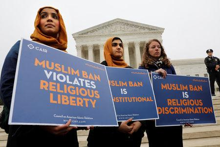 Protesters gather outside the U.S. Supreme Court in Washington, DC, U.S., April 25, 2018, while the court justices consider case regarding presidential powers as it weighs the legality of President Donald Trump's latest travel ban targeting people from Muslim-majority countries. REUTERS/Yuri Gripas