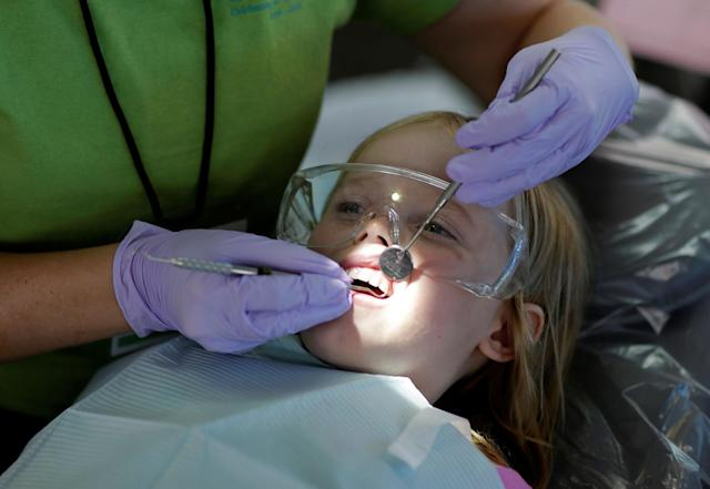 <p>Mallory Collins, 6, of Abington, Virginia, has her teeth cleaned at the Remote Area Medical Clinic in Wise, Va., July 21, 2017. (Photo: Joshua Roberts/Reuters) </p>