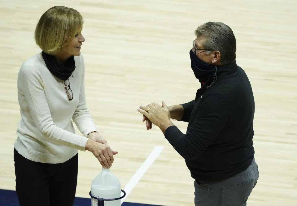 Connecticut head coach Geno Auriemma and associate head coach Chris Dailey sanitize their hands before an NCAA college basketball game against Providence at Harry A. Gampel Pavilion, Saturday, Jan. 9, 2021, in Storrs, Conn. (David Butler II/Pool Photo via AP)