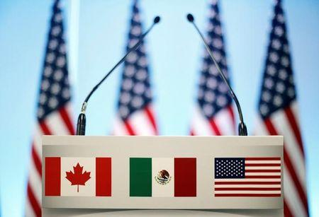 The flags of Canada, Mexico and the U.S. are seen on a lectern before a joint news conference on the closing of the seventh round of NAFTA talks in Mexico City