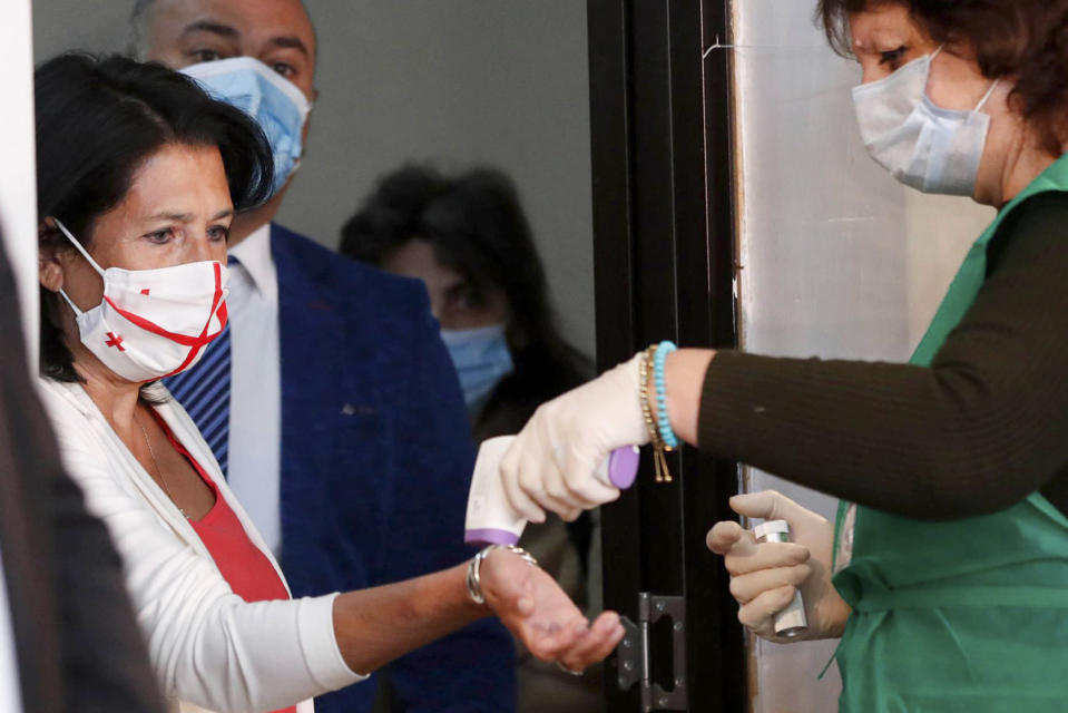 A medical worker checks the temperature of Georgia's President Salome Zurabishvili, left, wearing a face mask to help curb the spread of the coronavirus, as she enter a polling station during the parliamentary elections in Tbilisi, Georgia, Saturday, Oct. 31, 2020. The hotly contested election between the Georgian Dream party, created by billionaire Bidzina Ivanishvili who made his fortune in Russia and has held a strong majority in parliament for eight years, and an alliance around the country's ex-President Mikheil Saakashvili, who is in self-imposed exile in Ukraine. (Georgia's President Press office via AP)