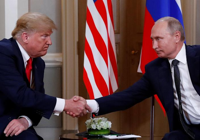 President Trump and Russian President Vladimir Putin shake hands as they meet in Helsinki. (Photo: Kevin Lamarque/Reuters)