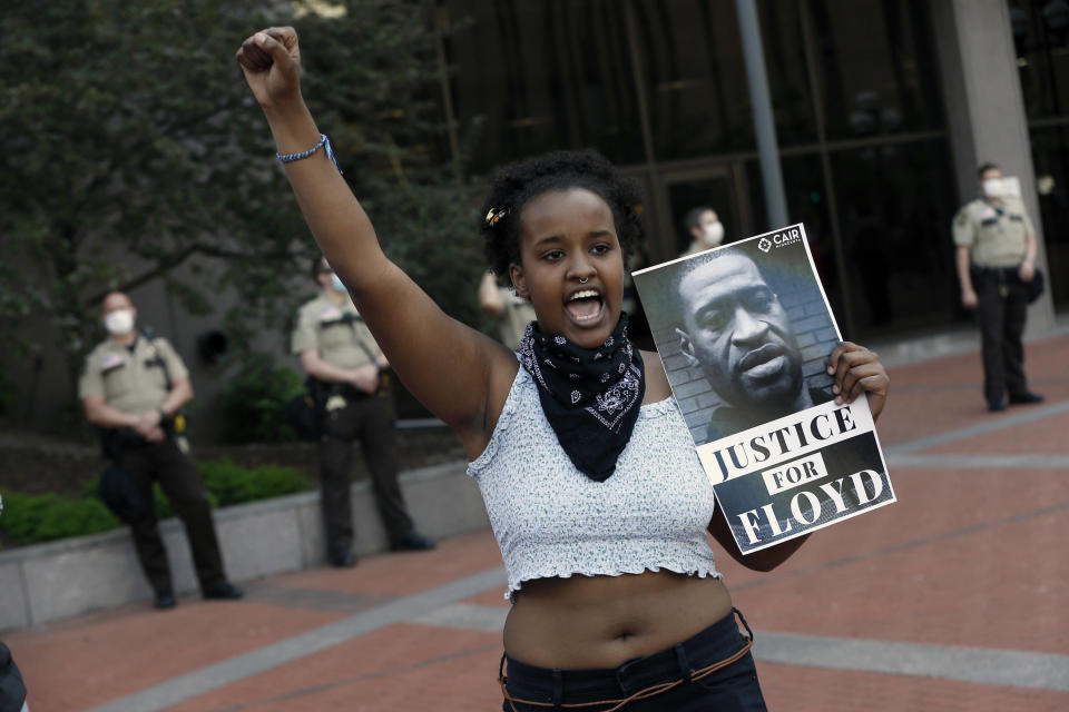 FILE - In this May 28, 2020 file photo, a protester holds a photo of George Floyd during a protest in Minneapolis over Floyd's death. Video from the body cameras of two officers charged in the death of Floyd is being made available for public viewing by appointment on Wednesday, July 15 but a judge has so far declined to allow news media organizations to publish the footage for wider distribution. (AP Photo/Jim Mone, File)