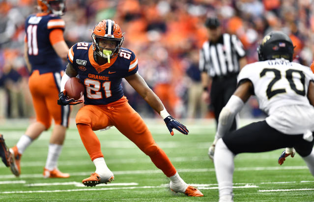 Syracuse running back Moe Neal, left, tries to elude Wake Forest defensive back Coby Davis (20) during the first half of an NCAA college football game in Syracuse, N.Y., Saturday, Nov. 30, 2019. (AP Photo/Adrian Kraus)