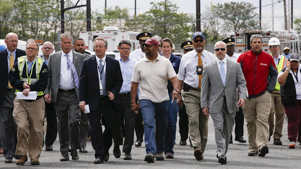 Philadelphia Mayor Michael Nutter (C, wearing red cap) arrives to give a news conference near the site of a derailed Amtrak train in Philadelphia, Pennsylvania May 13, 2015. Rescue workers on Wednesday sifted through twisted metal and other debris from the wreck of the Amtrak train that derailed in Philadelphia, killing at least six people and injuring scores of others, while investigators reviewed data to determine the cause of an accident. Nutter said authorities had not yet accounted for everyone aboard the train. REUTERS/Mike Segar