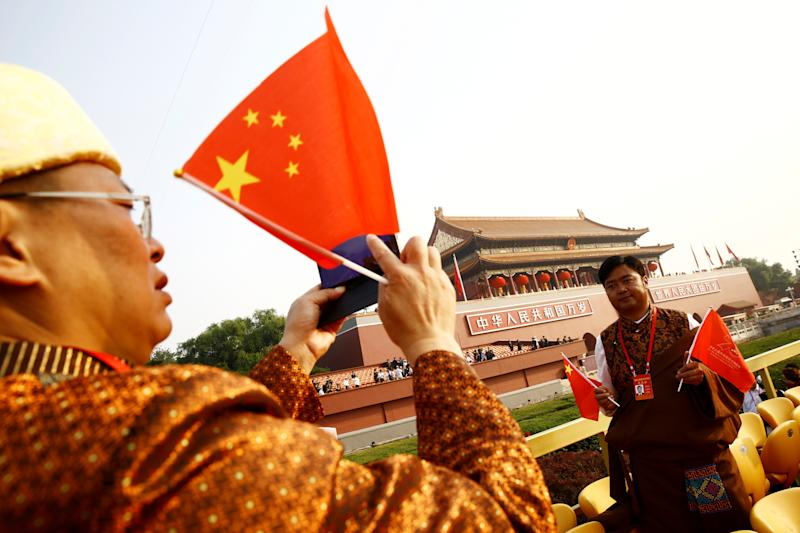 A Yunnan delegate holding Chinese flags poses for pictures with Tiananmen Gate in the background before a military parade marking the 70th founding anniversary of People's Republic of China, on its National Day in Beijing, China October 1, 2019. (Photo: Thomas Peter/Reuters)
