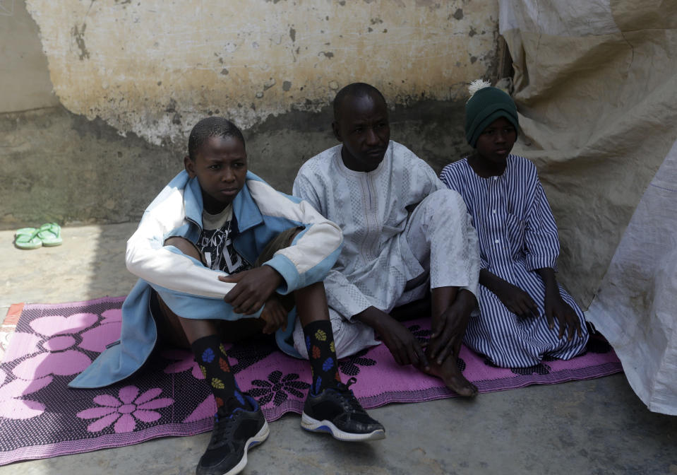 Hassan Mani, centre, father of freed schoolboy Abdulganiyu Hassan, outside his house in Kankara, Nigeria, Saturday Dec. 19, 2020. Nigeria's freed schoolboys have reunited with their joyful parents after being held captive for nearly a week by gunmen allied with jihadist rebels in the country's northwest. Relieved parents hugged their sons tightly on Saturday in Kankara, where more than 340 boys were abducted from the Government Science Secondary school on the night of Dec. 11. (AP Photo/Sunday Alamba)