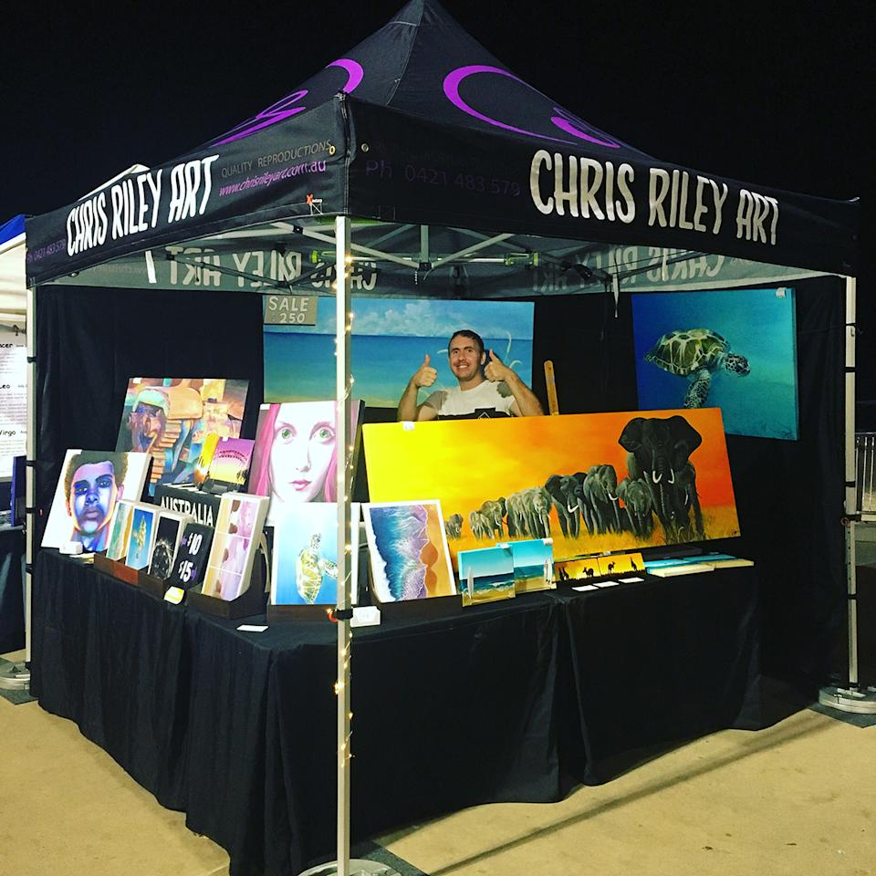 Australian painter Chris Riley selling his art at a market stall. Photo: supplied.