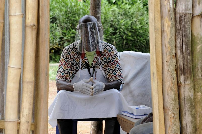 A man wearing a protective helmet as part of measures to fight against the Ebola virus, sits outside a clinic in Grand Gedeh, Liberia