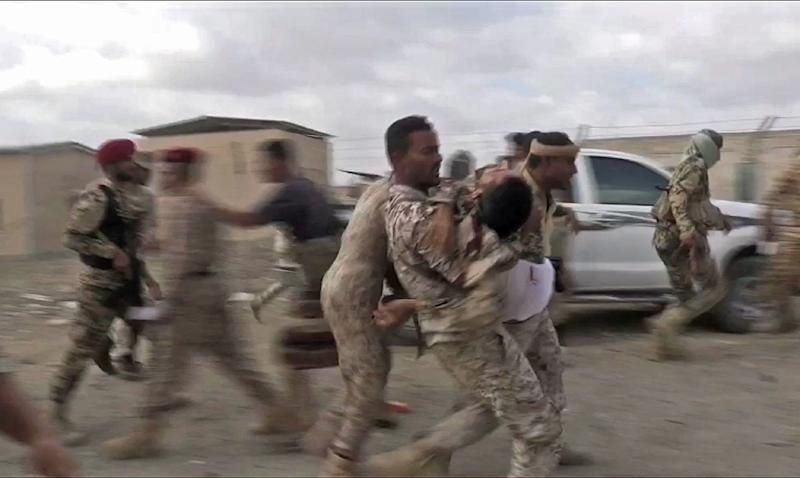 Soldiers carry a wounded comrade in the aftermath of the January 10, 2019 rebel drone attack on the Al-Anad air base in Yemen (AFP Photo/Nabil HASAN)