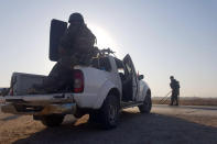 In this photo released by the Syrian official news agency SANA, Syrian troops deploy in the northern town of Tal Tamr, Monday, Oct 14, 2019. The move toward Tal Tamr came a day after Syria's Kurds said Syrian government forces agreed to help them fend off Turkey's invasion — a major shift in alliances that came after President Donald Trump ordered all U.S. troops withdrawn from the northern border area amid the rapidly deepening chaos. (SANA via AP)
