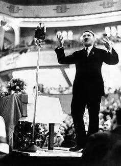 Adolf Hitler, dressed in a business suit, giving a speech.