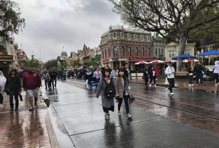 Visitors walk up and down Main Street in Disneyland, enjoying the last few hours until the park closes in Anaheim, Calif., Friday, March 13, 2020. Disneyland is closing its doors for the rest of the month, shuttering one of California's best-known attractions as the state hurries to stop the spread of the coronavirus. (AP Photo/Amy Taxin)