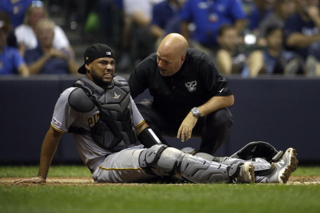 Pittsburgh Pirates' Elias Diaz, left, reacts as he is checked on by a trainer after suffering a leg injury during the fourth inning of a baseball game against the Milwaukee Brewers, Saturday, Sept. 21, 2019, in Milwaukee. Diaz was removed from the game. (AP Photo/Aaron Gash)