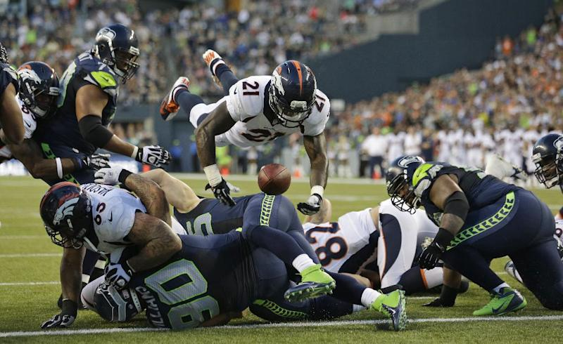 Denver Broncos running back Ronnie Hillman (21) fumbles as he goes over the top on a play against the Seattle Seahawks in the first half of a preseason NFL football game, Saturday, Aug. 17, 2013, in Seattle. The fumble was picked up by Seahawks' Brandon Browner, not seen, and returned for a touchdown. (AP Photo/Elaine Thompson)