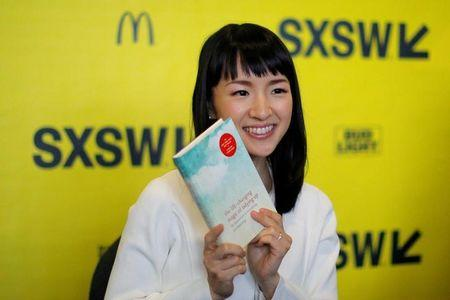 Japanese author and creator of the KonMari Method to declutter, Marie Kondo, poses with one of books for a fan's photograph during a book signing at the South by Southwest (SXSW) Music Film Interactive Festival 2017 in Austin, Texas, U.S., March 11, 2017. REUTERS/Brian Snyder