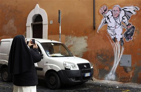 A nun takes a picture of a large drawing of Pope Francis depicting him as a superhero on a wall near the Vatican January 29, 2014. REUTERS/Alessandro Bianchi