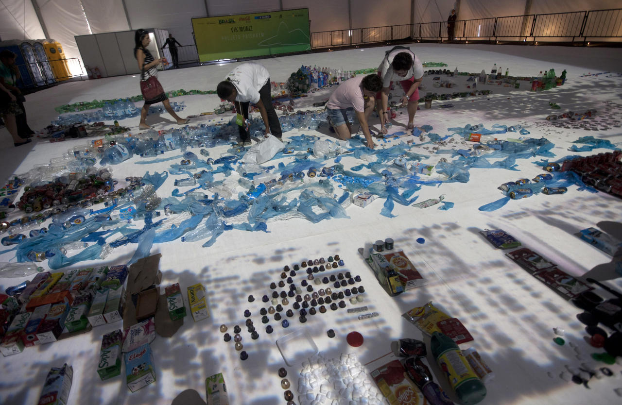 "People add waste products to the ""Landscape"" project by Brazilian artist Vik Muniz that recreates the image of Guanabara Bay in Rio de Janeiro, Brazil, Saturday, June 16, 2012. Muniz's project recreates city landmarks with recyclable materials donated by the public, who will be able to take their waste to the installation's tent between June 15 and 22, on the sidelines of the UN Conference on Sustainable Development, or Rio+20. (AP Photo/Silvia Izquierdo)"