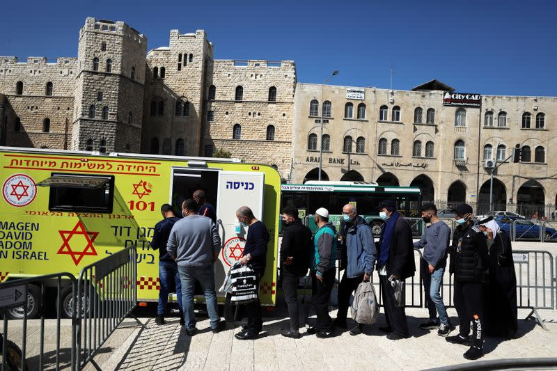 People queue to get vaccination against the coronavirus disease (COVID-19) at a mobile vaccination vehicle, in Jerusalem