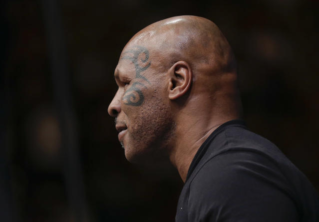 Mike Tyson makes his way up to the octagon to congratulate Glover Teixeira after a UFC 160 mixed martial arts light heavyweight bout, Saturday, May 25, 2013, in Las Vegas. (AP Photo/Julie Jacobson)