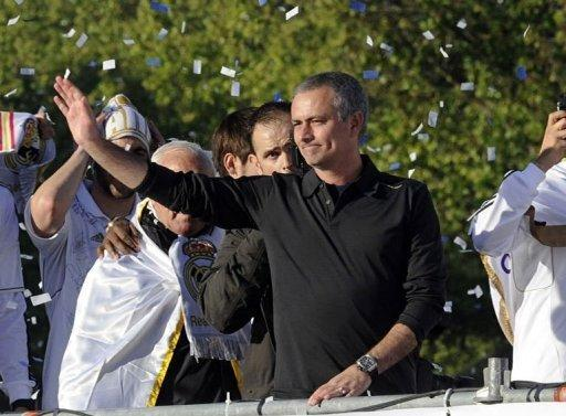 Real Madrid's Portuguese coach Jose Mourinho celebrates on an open bus at Cibeles square in Madrid. Thousands of jubilant Real Madrid fans swamped the centre of the Spanish capital on Thursday to see their heroes parade in an open-top bus in celebration of their league title success