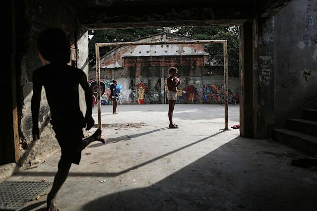 <p>A boy runs in a set of occupied buildings in the Mangueira favela, May 2, 2017, in Rio de Janeiro. (Photo: Mario Tama/Getty Images) </p>