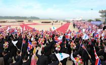 The North's unique brand of choreographed mass adulation was on full display as hundreds of people on the tarmac waved North Korean flags and unification ones depicting an undivided peninsula