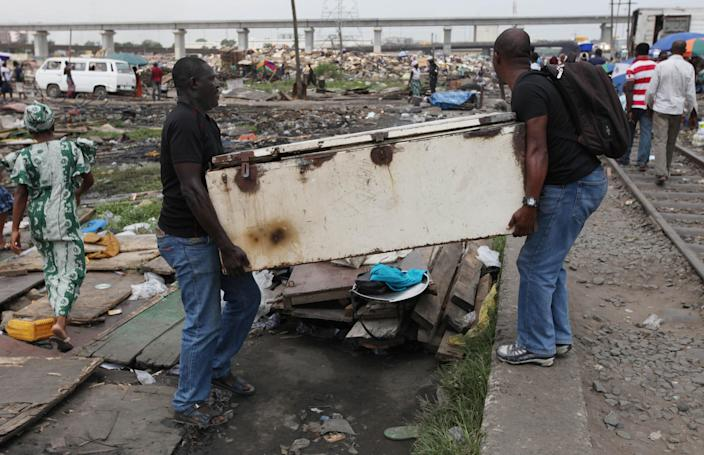 In this image taken Thursday Feb. 28, 2013 men carry a salvaged refrigerator from the site of demolished houses at Ijora Badia slum in Lagos, Nigeria. The bulldozers arrived at dawn to this neighborhood of shanty homes and concrete buildings in Nigeria's largest city, followed by police officers in riot gear carrying Kalashnikov assault rifles. The police banged on doors, corralling the thousands who live in Ijora-Badia off to the side as the bulldozers' blades tore through scrap-lumber walls, its track grinding the possessions inside into the black murk of swamp beneath it. It left behind only a field of debris that children days later picked through, their small hands dodging exposed rusty nails to pull away anything of value left behind. (AP Photo/Sunday Alamba)