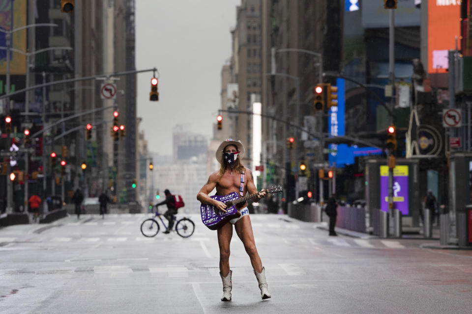 "Street performer Robert John Burck, known as The Naked Cowboy, poses for photos in New York's Times Square, Thursday, April 9, 2020, during the coronavirus epidemic. He is wearing a mask and his guitar is adorned with stickers that read, ""Trump Keep America Great."" The New York City immortalized in song and scene has been swapped out for the last few months with the virus version. In all the unknowing of what the future holds, there's faith in that other quintessential facet of New York City: that the city will adapt. (AP Photo/Mark Lennihan)"