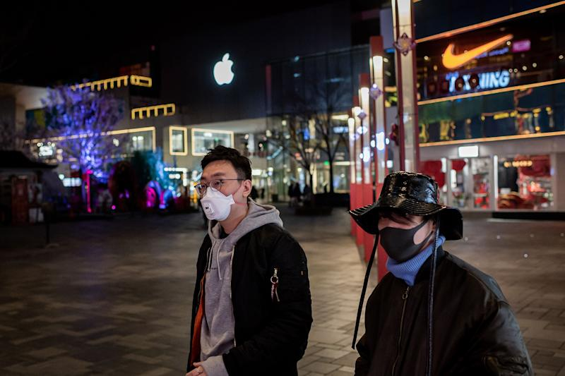 People wearing a protective facemask to protect against the COVID-19 coronavirus walk past an Apple store (top L) and a Nike shop (top R) outside of a nearly empty shopping mall, minutes after rush hour, in Beijing on February 24, 2020. - The novel coronavirus has spread to more than 25 countries since it emerged in December and is causing mounting alarm due to new outbreaks in Europe, the Middle East and Asia. (Photo by NICOLAS ASFOURI / AFP) (Photo by NICOLAS ASFOURI/AFP via Getty Images)