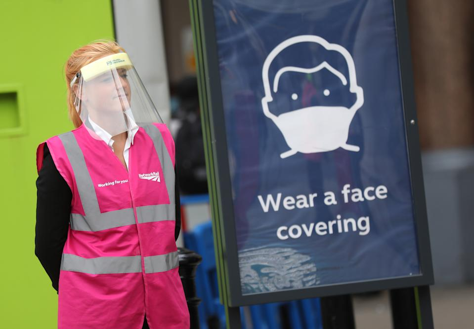 A Network Rail member of staff wearing a protective visor stands next to a sign telling commuters to wear a face covering while using public transport at Charing Cross Station, as London prepare to reopen to the public when the lifting of further lockdown restrictions in England comes into effect on Saturday. Picture date: Friday July 3, 2020.