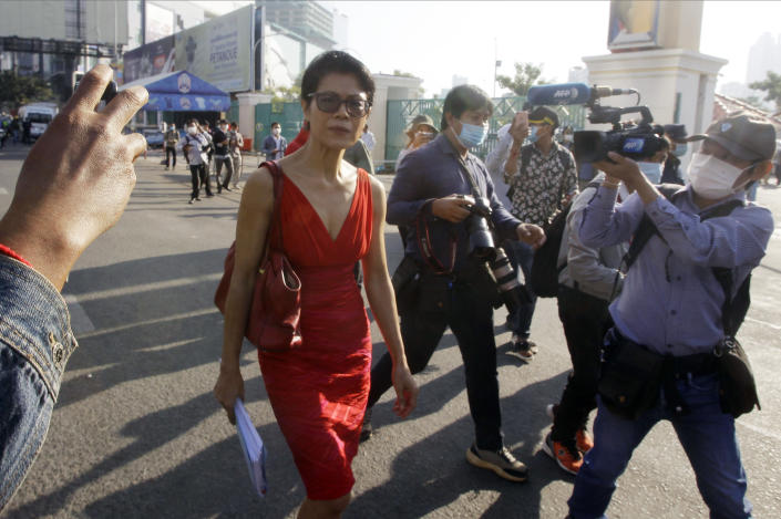 Theary Seng, center, a Cambodian-American lawyer, walks in front of Phnom Penh Municipal Court in Phnom Penh, Cambodia, Thursday, Jan. 14, 2021. Theary Seng said Thursday she was being persecuted for her political opinion as she and dozens of other government critics charged with treason and other offenses returned to court in a trial criticized by rights advocates. (AP Photo/Heng Sinith)