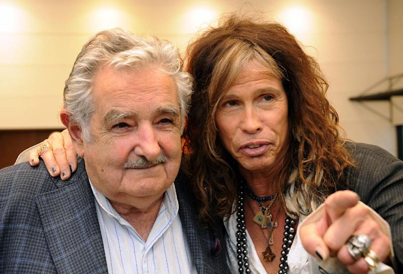 In this picture released by Uruguay's Press Office, President Jose Mujica, left, poses with Aerosmith's led singer Steven Tyler after receiving an autographed guitar as a gift at the presidential house in Montevideo, Uruguay, Tuesday, Oct. 8, 2013. The band will perform on Wednesday as part of their Latin America tour. (AP Photo/Uruguay Press Office, Alvaro Salas)