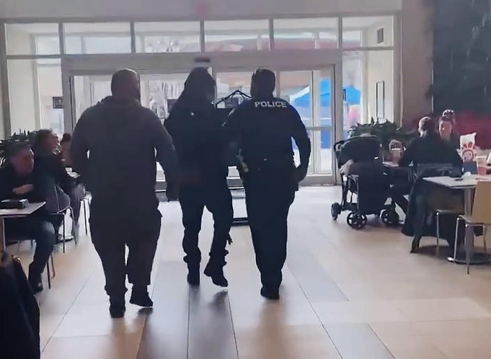 Police detain a Black man at a Virginia mall as he and his family were eating. (Kiara Love via Facebook)