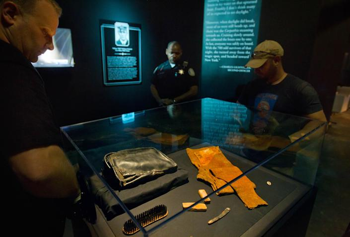 """Workers place a casing over the personal effects of William Murdoch, the bridge officer aboard the Titanic, before an exhibition opens to the public Tuesday, April 3, 2012, in Atlanta. From the pitch-black depths 2½ miles beneath the North Atlantic, salvagers of the Titanic made a notable discovery when they located the personal effects of Murdoch, the bridge officer who tried in vain to keep the doomed ship from colliding with an iceberg. The artifacts, including a shoe brush, straight razor and pipe, are the first to be specifically to Murdoch, a central figure in the disaster who gained added notoriety after James Cameron's polemical portrayal of him in the 1997 blockbuster movie """"Titanic."""" (AP Photo/David Goldman)"""
