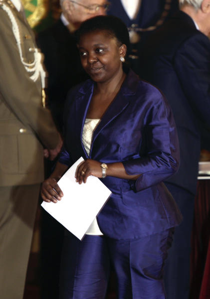 In this photo taken on April 28, 2013 photo Integration Minister Cecile Kyenge walks moments after taking oath during the swearing in ceremony at the Quirinale Presidential Palace, in Rome. The appointment of Italy's first black cabinet minister was initially hailed as a giant step forward for a country that has long been ill at ease with its increasing immigrant classes. Cecile Kyenge's new job has instead exposed Italy's ugly race problem, an issue that flares regularly on the football pitch with racist taunts and in the rhetoric of xenophobic political parties but has come to the fore anew as a shaky coalition government tries to bring Italy out of its economic doldrums. Kyenge, 48, was born in Congo and moved to Italy three decades ago to study medicine. An eye surgeon, she lives in Modena with her Italian husband and two children and was active in local center-left politics before winning a seat in the lower Chamber of Deputies in February elections. (AP Photo/Domenico Stinellis)