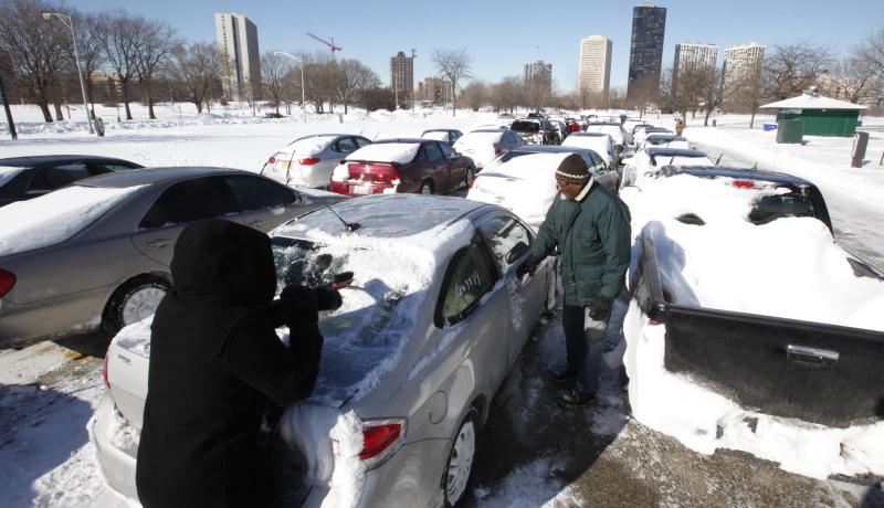 Jarrod Leak, left, who was stranded on Lake Shore Drive during Tuesday night's blizzard, cleans off his car with the help of his father, Avery, in a vehicle recovery lot one day after the the third largest snowfall in Chicago's history, Thursday, Feb. 3, 2011. The next problem Leak faces is how to get his car out of the lot where other unclaimed cars surround his. (AP Photo/Charles Rex Arbogast)