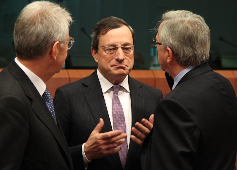 President of the European Central Bank Mario Draghi, center, gestures, as he talks with Italy's Prime and Finance Minister Mario Monti, left, and Luxembourg's Prime Minister and chairman of the Eurogroup, Jean-Claude Juncker, during the Eurogroup ministerial meeting at the European Council building in Brussels, Monday, May 14, 2012. (AP Photo/Yves Logghe)